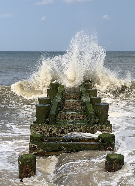 Wave breaking over breakwater.