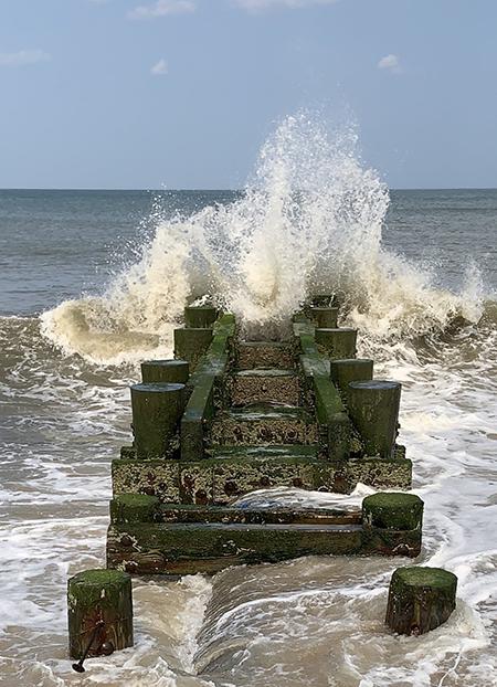 Wave breaking over breakwater.